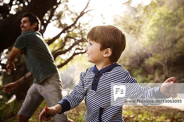 Glücklicher Junge mit Vater im Wald