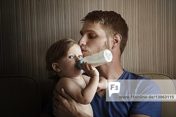 Baby boy drinking milk while father kissing him at home