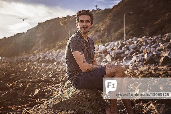 Nachdenklicher Mann schaut weg,  während er auf einem Felsen am Strand sitzt