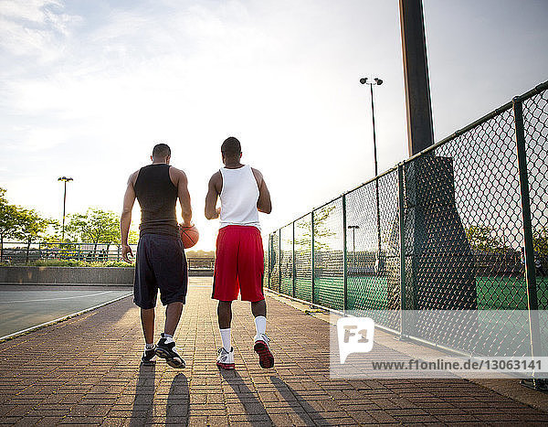 Rear view of basketball players walking in court