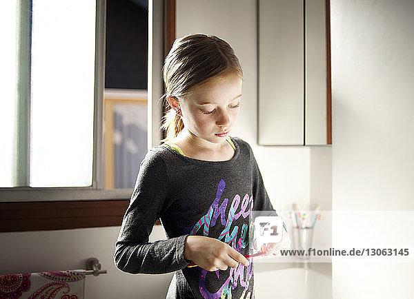 Mädchen putzt Zahnpasta auf Zahnbürste im Badezimmer