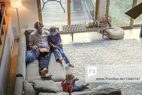 Hochwinkelansicht einer Familie  die sich zu Hause auf dem Sofa entspannt
