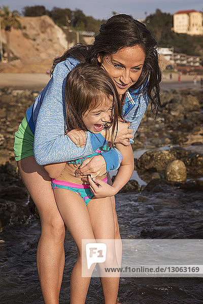 Glückliche Mutter umarmt Mädchen am Strand