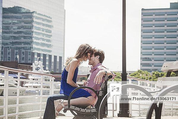 Romantisches Paar auf Bank am Fluss sitzend