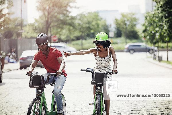 Verspieltes Paar beim Radfahren auf der Straße