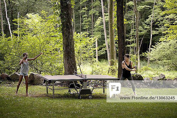 Paar spielt Tischtennis im Wald