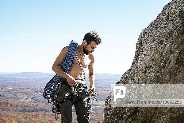 Mann betrachtet Kletterausrüstung  während er an einer Felsformation steht