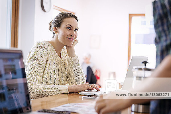 Smiling woman looking at man while using laptop at home
