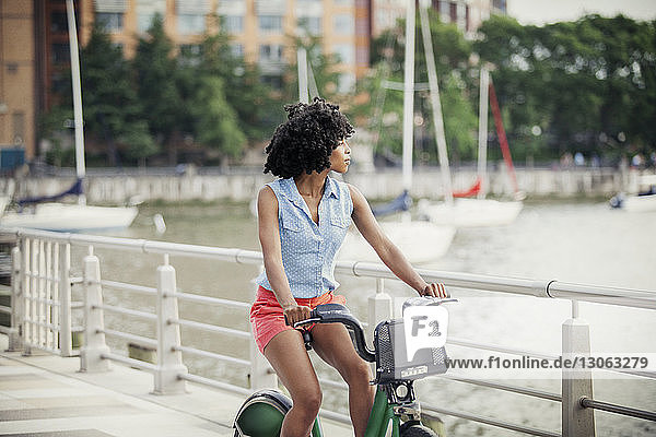 Woman looking away while cycling on promenade against river