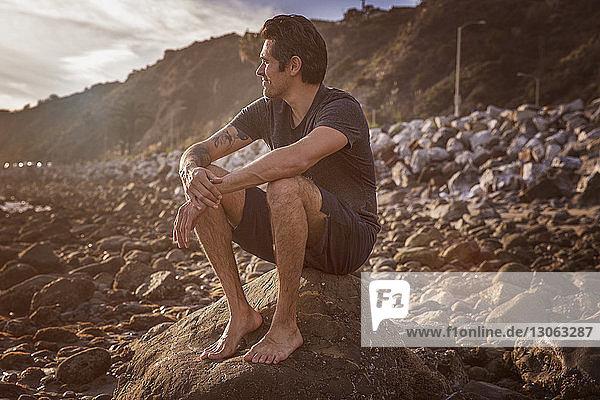 Mann schaut weg  während er auf einem Felsen am Strand sitzt