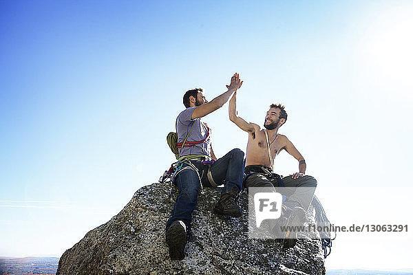 Glückliche Freunde machen High-Five  während sie auf einem Felsen vor klarem Himmel sitzen