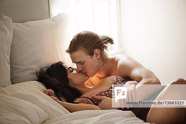 Zärtliches Paar küsst sich zu Hause im Schlafzimmer