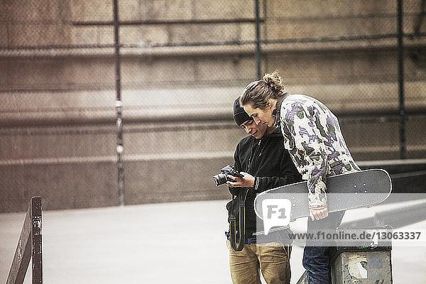 Freunde schauen in die Kamera  während sie im Skateboard-Park stehen