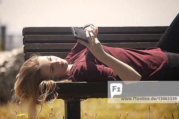 Frau benutzt Mobiltelefon  während sie auf einer Parkbank liegt