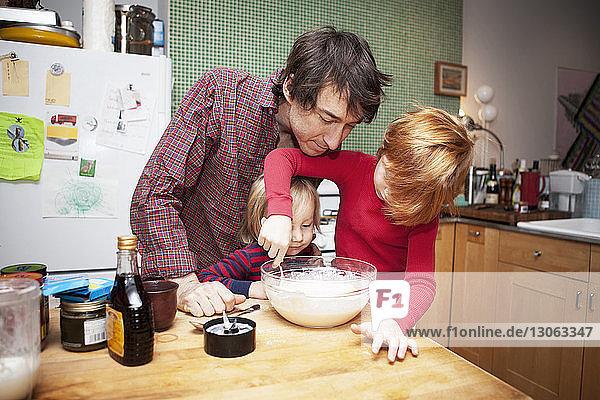 Vater und Söhne kochen zu Hause in der Küche