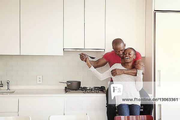 Verspieltes Paar genießt das Kochen in der Küche
