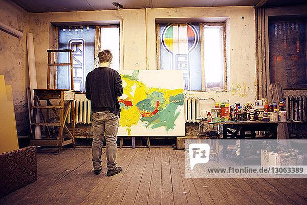 Rückansicht eines in der Werkstatt stehenden männlichen Künstlers