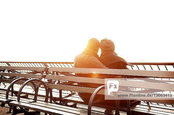 Rear view of couple sitting on bench against sky during sunset