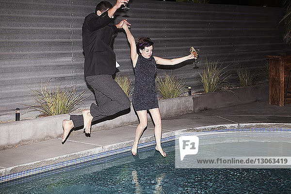 Paar mit Händchenhalten beim Springen im Schwimmbad