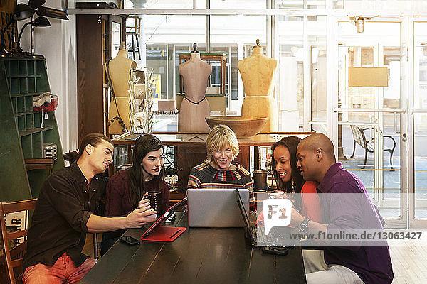 Freunde schauen auf den Laptop  während sie im Bekleidungsgeschäft sitzen