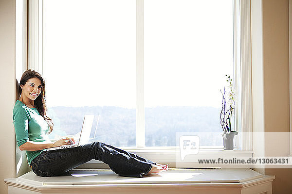 Side view of woman sitting on window and using laptop
