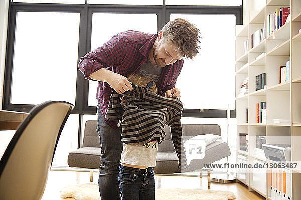 Vater hilft Tochter beim Tragen eines Pullovers zu Hause