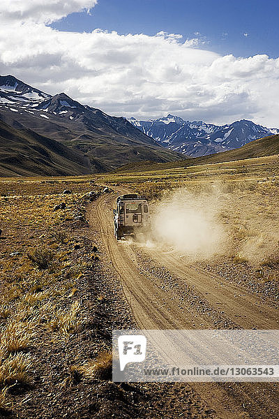 Off-road vehicle on dirt road against cloudy sky