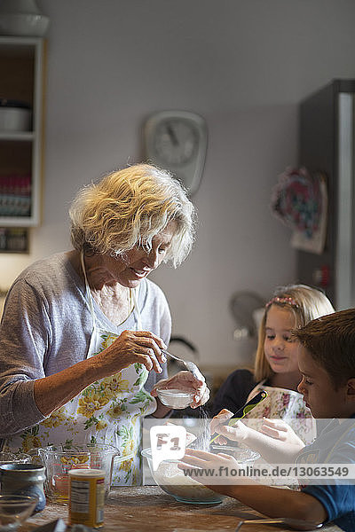 Woman adding sugars in dough while making cookies with children in kitchen