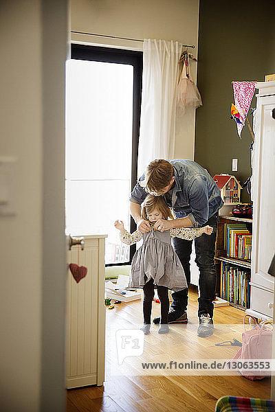 Vater hilft Tochter beim Anziehen zu Hause