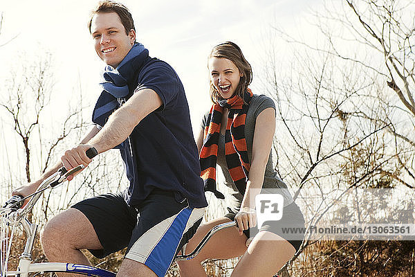 Portrait of cheerful couple riding tandem bicycle against sky