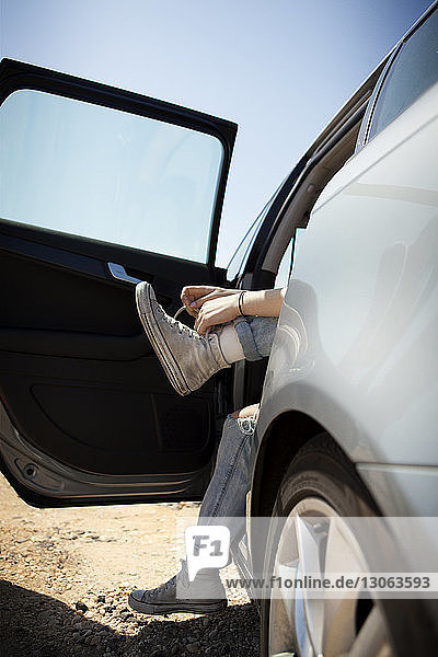 Low section of woman tying shoelace while sitting in car