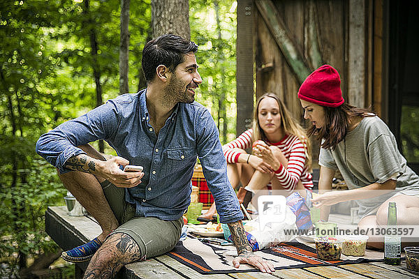 Man looking away while sitting with friends on porch in forest