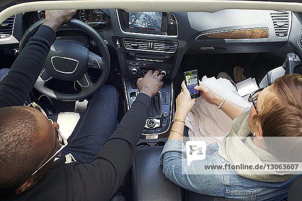 Draufsicht einer Frau  die ein Smartphone benutzt  während sie mit ihrem Freund im Auto unterwegs ist