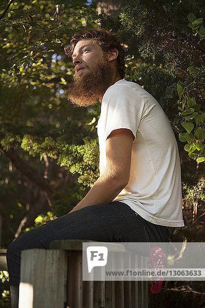 Mann schaut weg  während er auf einer Holzkonstruktion im Wald sitzt