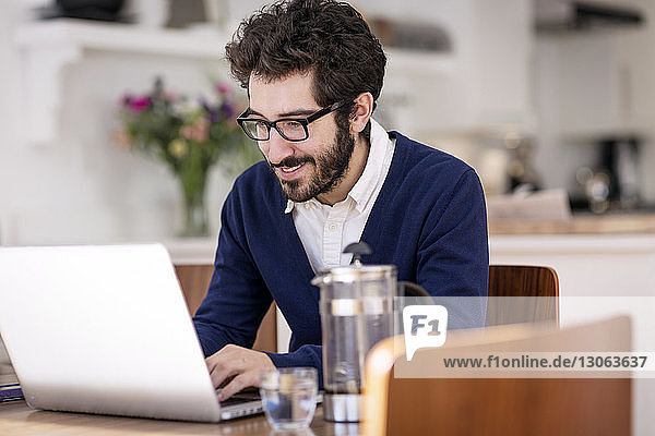 Man using laptop computer while sitting at table in home