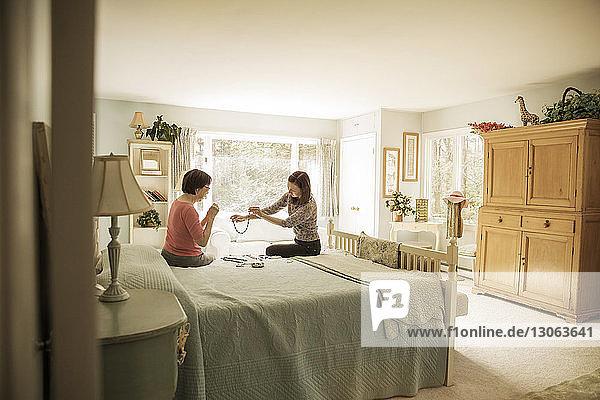 Mutter und Tochter schauen auf die Halskette  während sie auf dem Bett sitzen