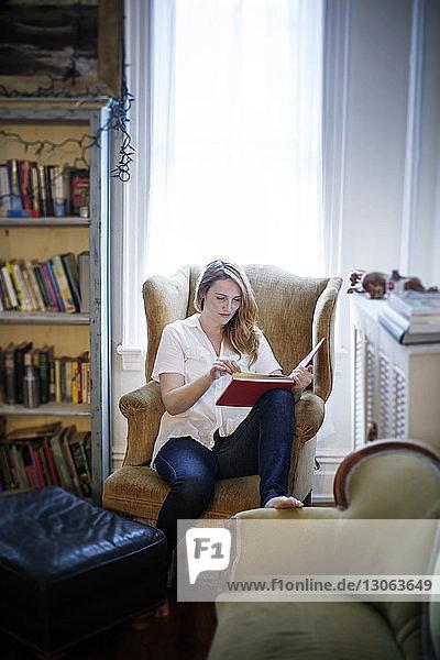 Frau liest Buch  während sie zu Hause auf einem Sessel sitzt