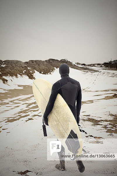 Rear view of man carrying surfboard while walking on snow covered field