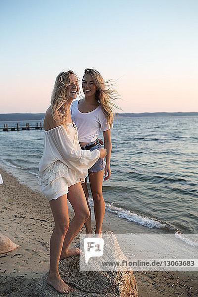 Glückliche Freunde stehen auf einem Felsen am Strand vor klarem Himmel