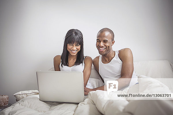 Happy couple using laptop computer while sitting on bed