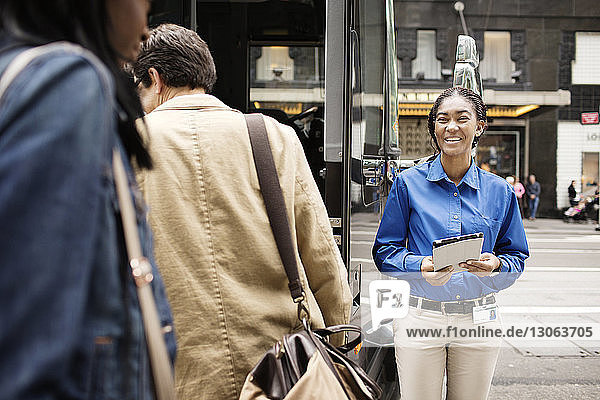 Cheerful guide looking at passengers while standing at street