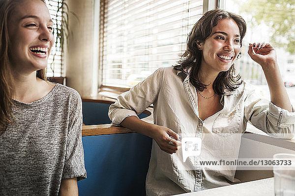 Lächelnde Freunde unterhalten sich  während sie im Restaurant sitzen