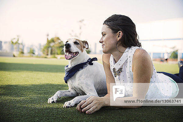Smiling woman lying with dog on grassy field against clear sky at park