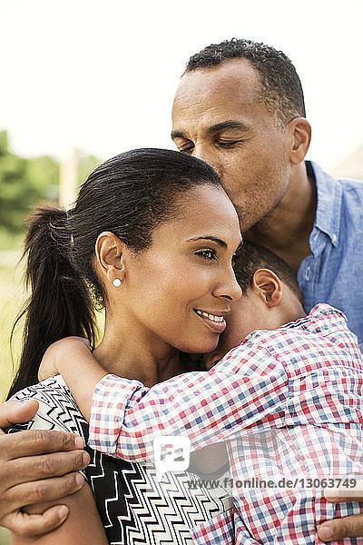 Mann küsst Familie mit geschlossenen Augen im Hinterhof