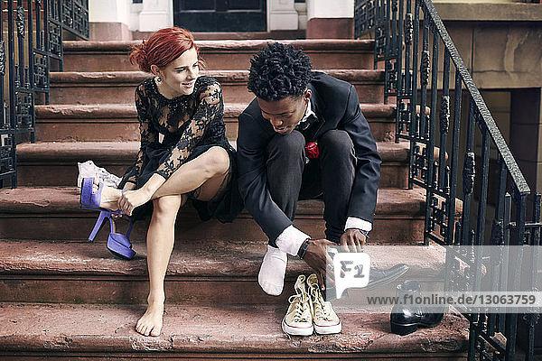 Paar Schuhe beim Sitzen auf Stufen ausziehen
