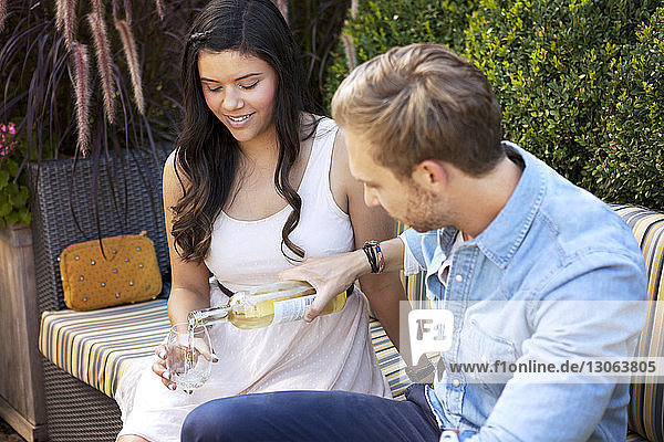 Man serving wine to female friend while sitting on sofa at building terrace