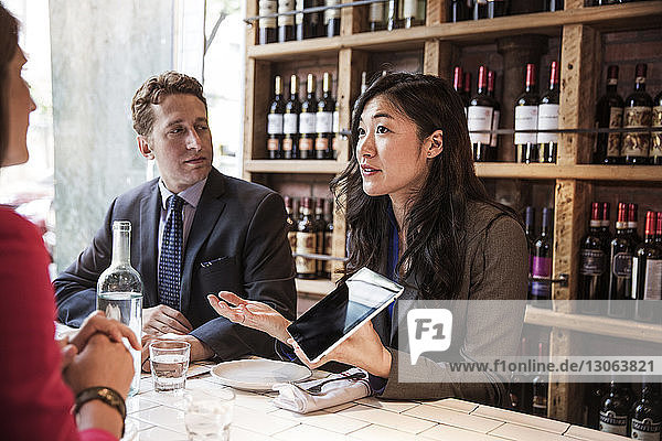 Woman showing tablet computer to colleagues while discussing in bar