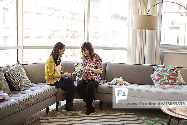 Pregnant woman showing baby clothes to friend while sitting on sofa at home