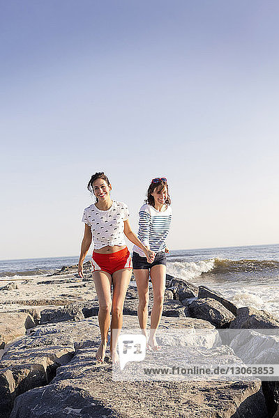 Happy friends holding hands while walking on rocks at beach