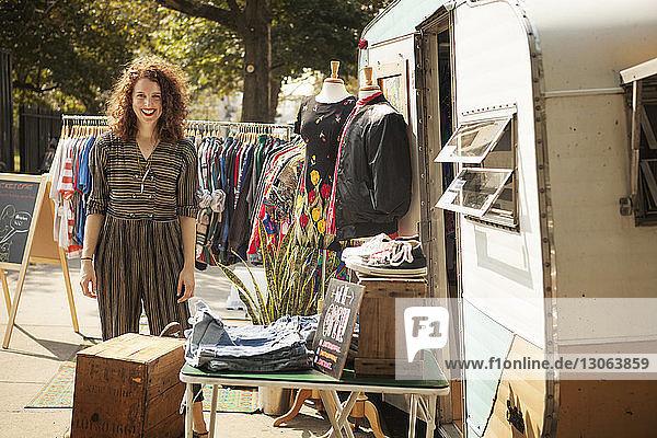 Portrait of woman standing by camper van